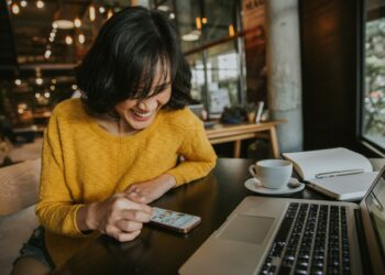 paket internet unlimited paket internet unlimited pandemi - young hipster woman smiling sitting in coffee shop using smartphone smiling technology happy internet t20 XznLE6 350x250 - Cara Memilih Paket Internet Unlimited Kala Pandemi