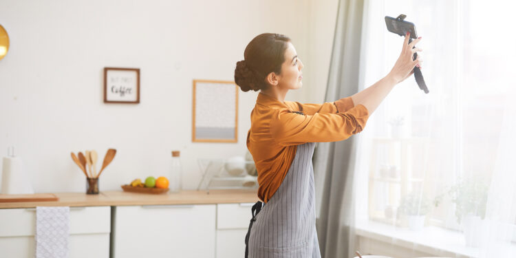 Side view portrait of beautiful young woman holding smartphone while filming story video for social media channel, copy space hp dengan fitur video 4k - HP dengan Fitur Video 4K yang cocok untuk vlog 750x375 - 7 Rekomendasi HP dengan Fitur Video 4K Terbaik, Cocok Buat Nge-vlog