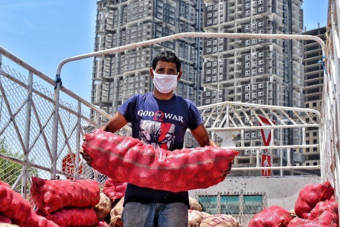 ekspor arab saudi memasarkan produk ukm di arab saudi - man wearing a protective face mask unloading a very heavy sack of red onions from his truck they are t20 4ejE9R - Kiat Memasarkan Produk UKM di Arab Saudi